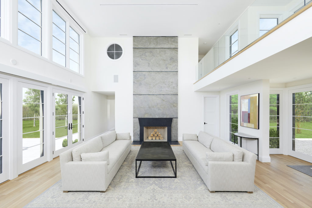 Great room of modern farmhouse in Sagaponack, New York, is flooded with light from the expanses of glass and clerestory windows